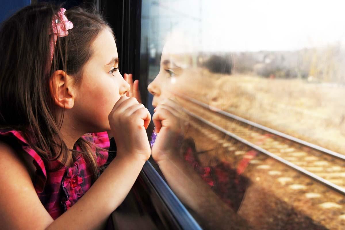 девочка смотрит в окно поезда